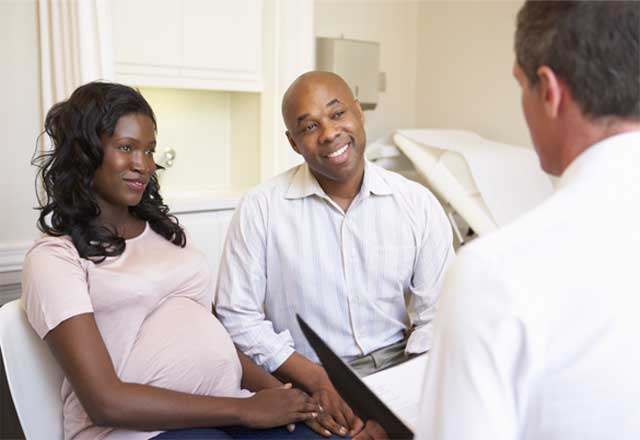 pregnant woman and her male partner speak with physician