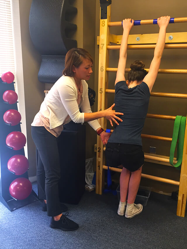 Lien helps Sophie with Schroth exercises