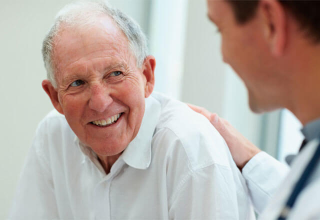 Elderly man smiling at doctor