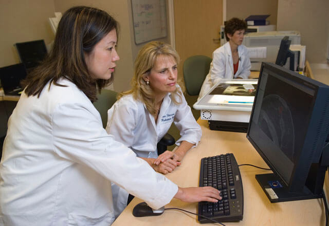 cancer care providers view patient scans on a computer