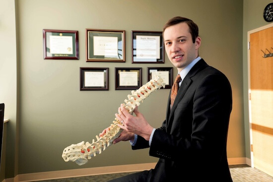 Neurosurgeon holding model of spine