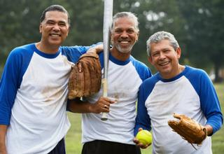 three men posing with baseball glove and bat