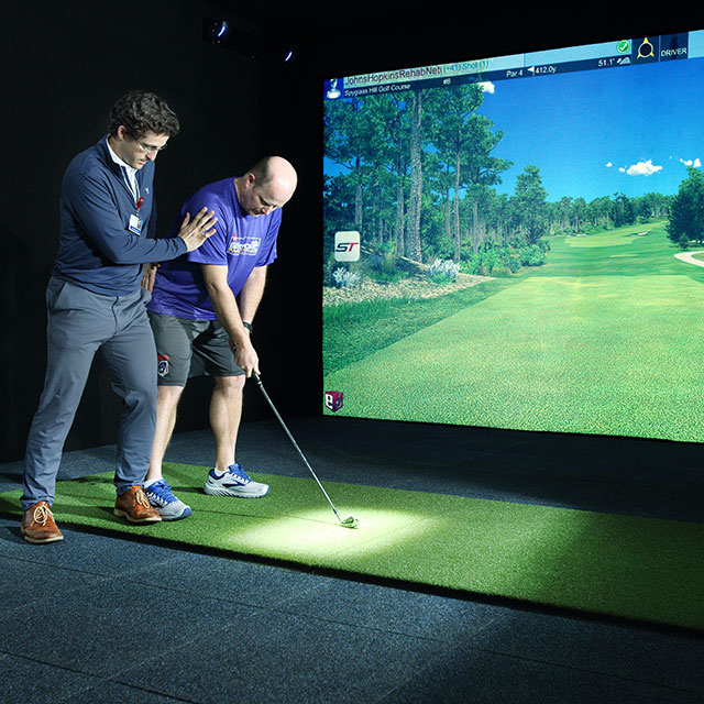 A physical therapist uses a simulator to help a patient with his golf swing