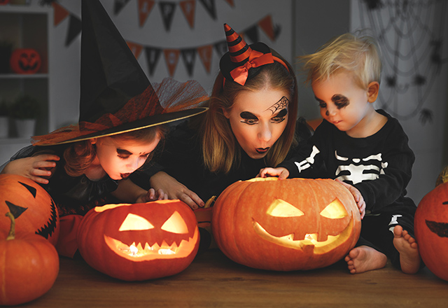 A mother and her two small children gather around lit jack-o-lanterns.