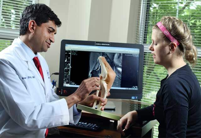 Dr. Sameer Dixit, sports medicine expert, speaks with female athlete about her ACL injury.