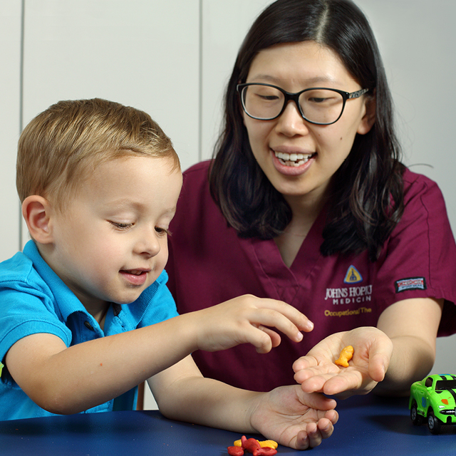 A photo shows occupational therapist Yun Kim helping a patient improve fine motor skills.