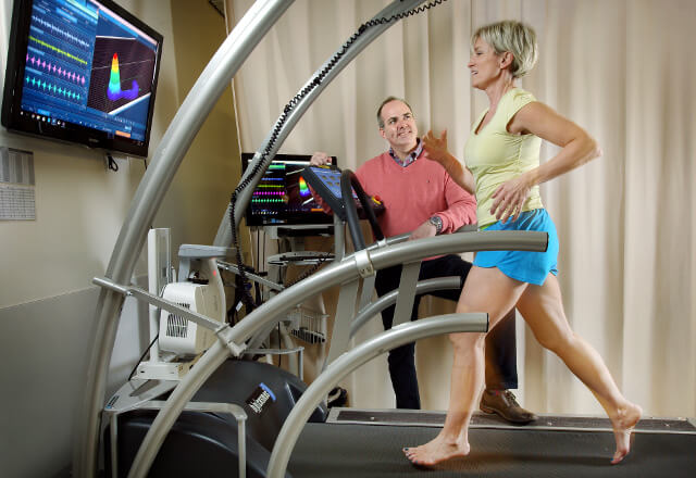 A physical therapist watching a patient exercise on a treadmill