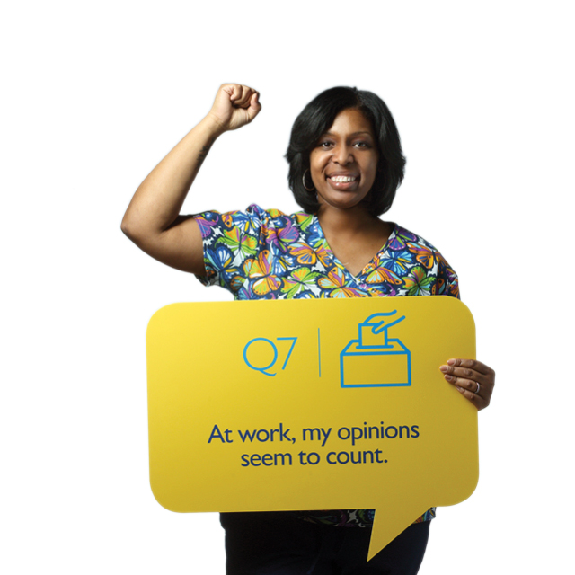"Carla Johnson, case manager for JH Home Care Group, raises her fist and holds a sign that says, ""At work, my opinions seem to count."""