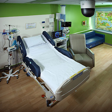 A bed in the new pediatric epilepsy monitoring unit with a computer, medical devices and IV pole next to it, a lounge chair and couch are next to bed and a world map hangs on the wall in the background.