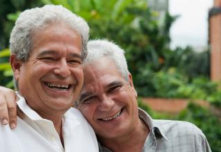 older couple with arms around each other smiling