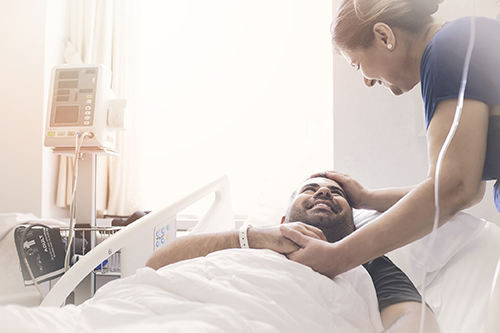 man smiling in hospital bed