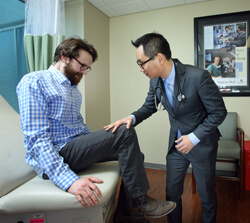 Tae Chung tests Matt Darnell's reflexes on a follow-up visit for myositis care. Darnell says he wishes more patients with his condition were aware of the benefits of early physical activity.