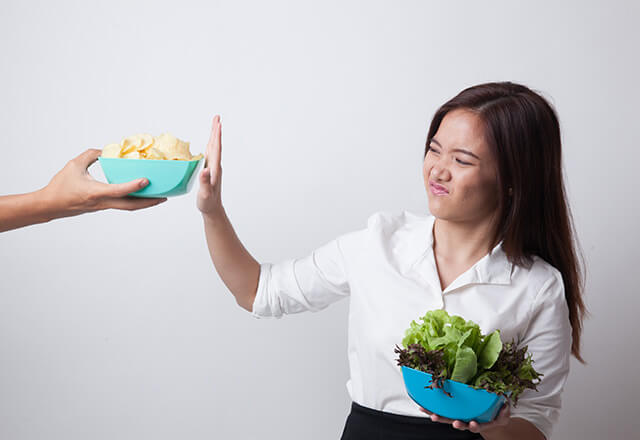 Woman turning away chips in favor of a salad