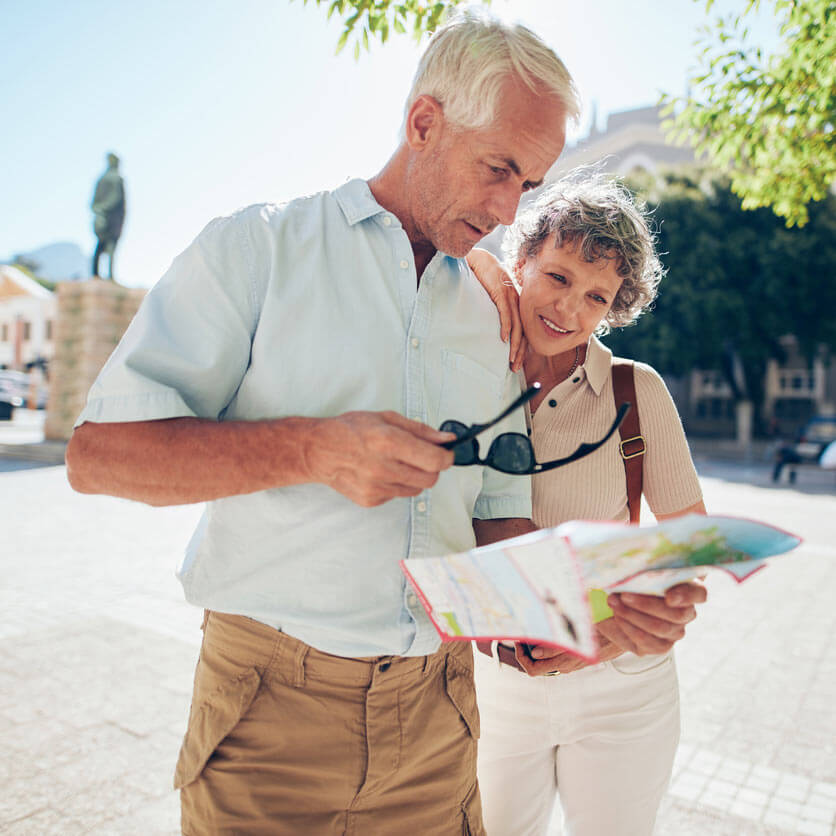Tourist couple consulting a map in a scenic town square
