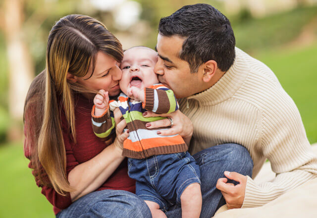 two parents kissing their infant on the cheek at the same time in a park