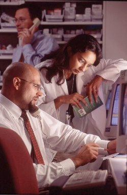Two hospital staff reviewing information on computer