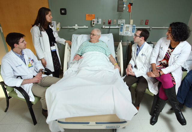 Residents and faculty talking to a patient