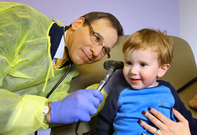 Peter Mogayzel examines a child's ear in the Johns Hopkins Children's Center
