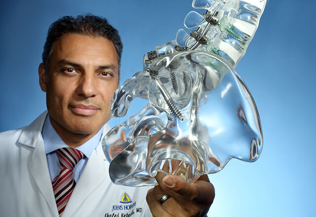 Dr. Khaled Kebaish holding a model of a spine