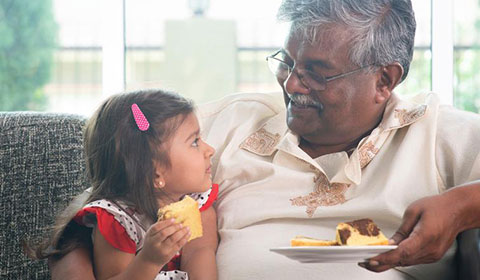 Grandfather and granddaughter eating dessert together.