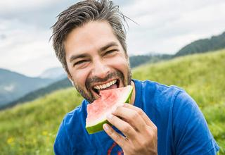 A middle aged man eating a watermelon slice in the middle of a field.