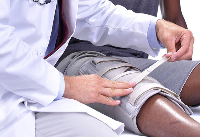 Doctor adjusting a knee brace for a patient.