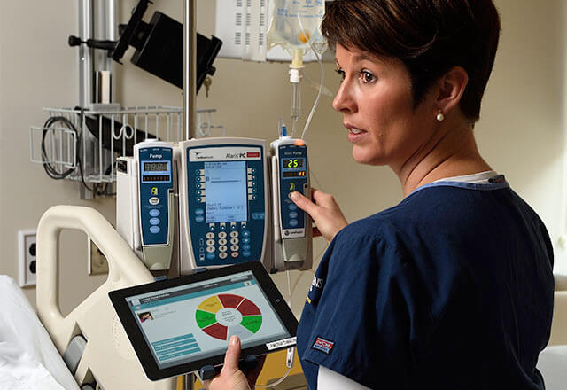 female nurse using a clinical tablet app in the ICU