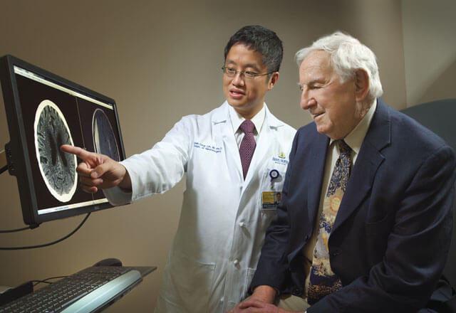 physician explains MRI scan to older patient