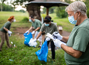 Photo shows a group of volunteers wearing face masks and practicing social distancing during a neighborhood cleanup event.