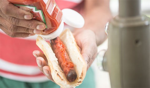 Adding ketchup to a hotdog.