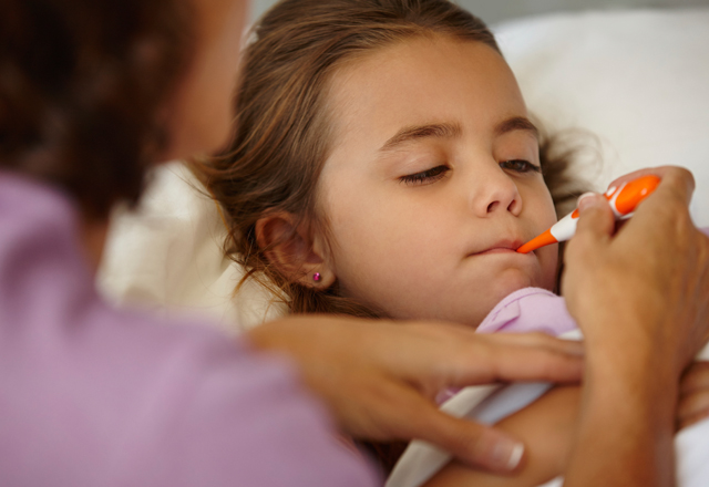 girl with a thermometer in her mouth