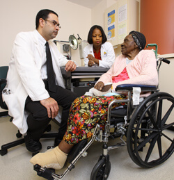 Victor Urrutia and Brenda Johnson discuss stroke rehab with a patient.