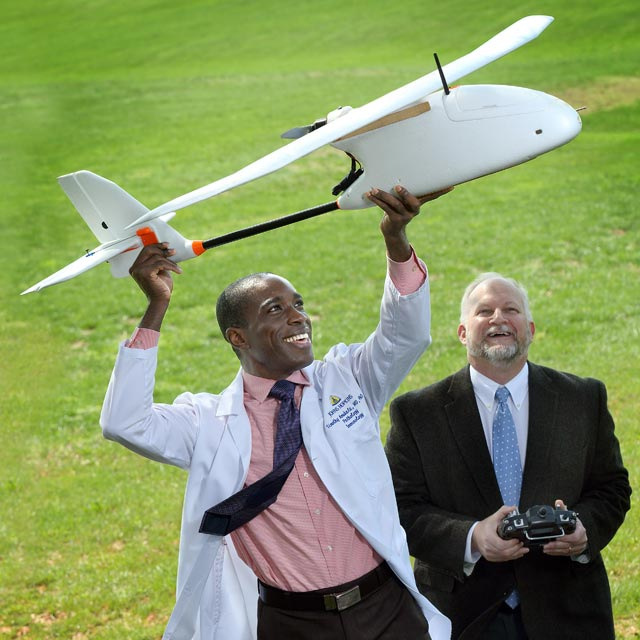 Pathologist Timothy Amukele, left, holds an unmanned aerial vehicle next to Robert Chalmers.