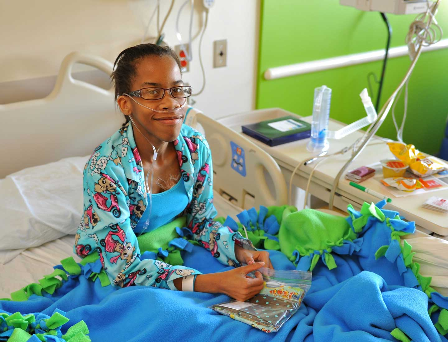 A young patient, LaParis Harris, settles into her light-filled private room.