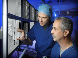 Phillippe Gailloud, left, and Rafael Tamargo discuss an arteriovenous malformation. The rare finding requires early intervention for the best outcomes.