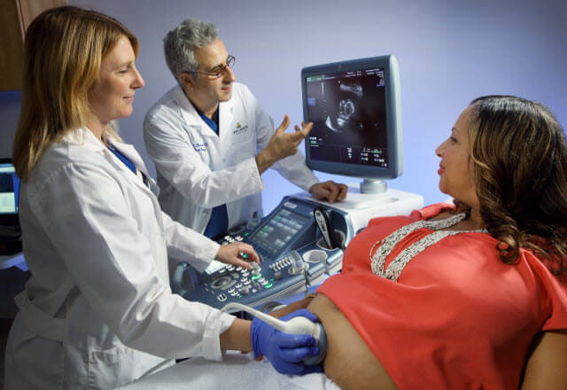 pregnant woman and sonographer and Dr. Baschat in a patient treatment room