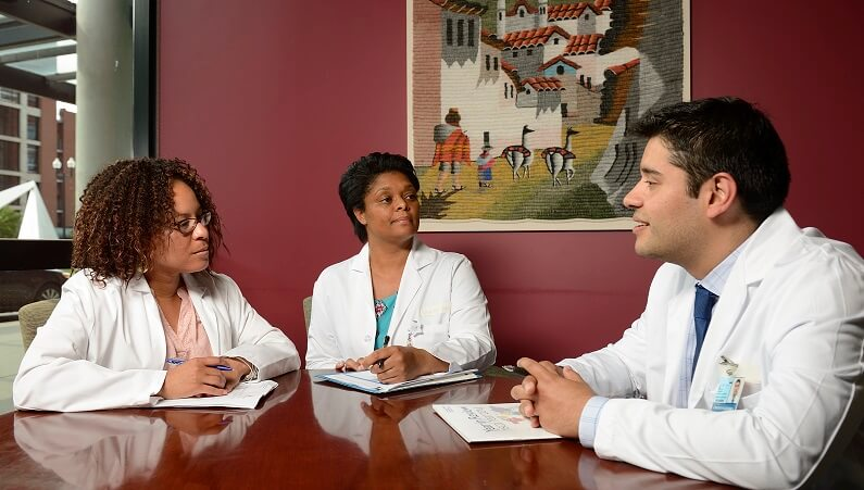 three people at table wearing white coats