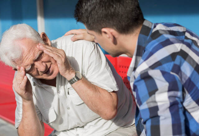 older man with dizziness helped by younger man