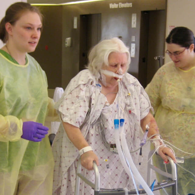 Therapists helping a woman walk in an ICU