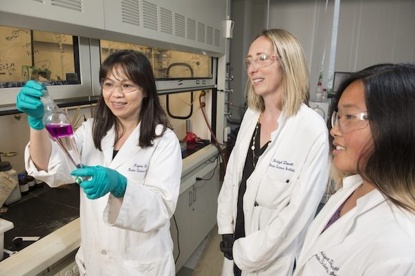 three scientists in white lab coats discussing an experiment