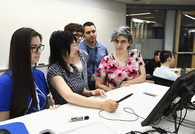 A faculty member works with graduate students on a computer.