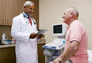 Older patient sits in a patient room and discusses health concerns with his doctor.