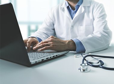 Photo of doctor typing on computer.
