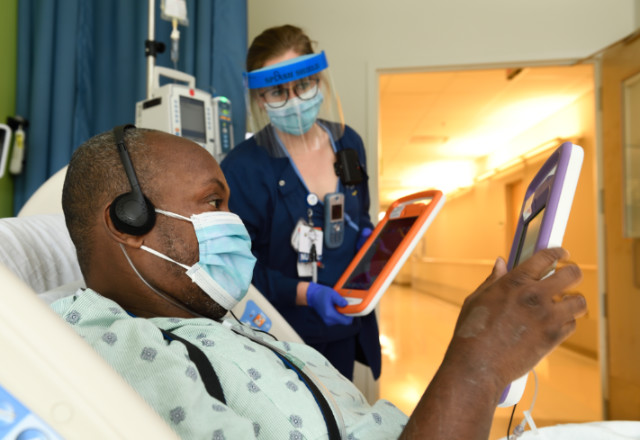 Nurse Shelby Cahill helps Shawn Hoke, a patient in the Progressive Cardiac Care Unit, navigate the MyChart Bedside tablet