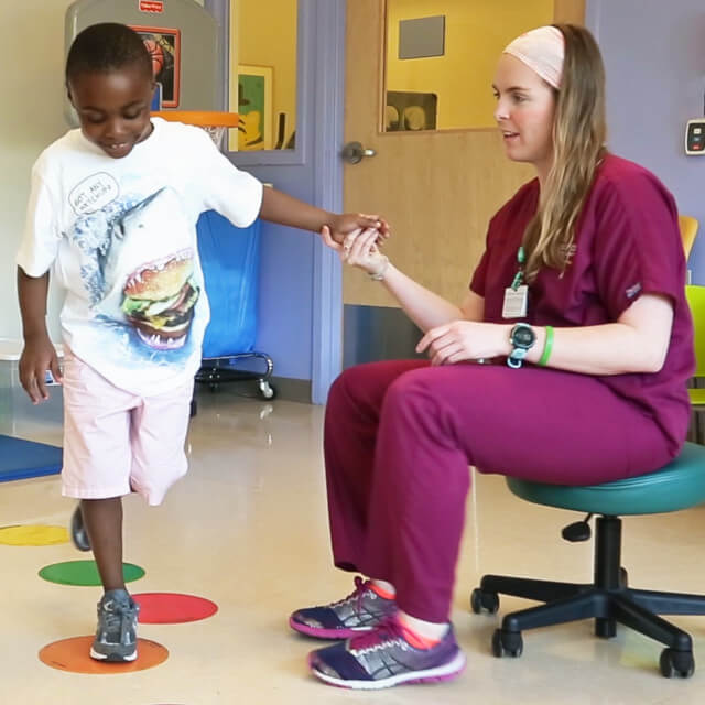 Pediatric occupational therapist helping a boy hop on circles