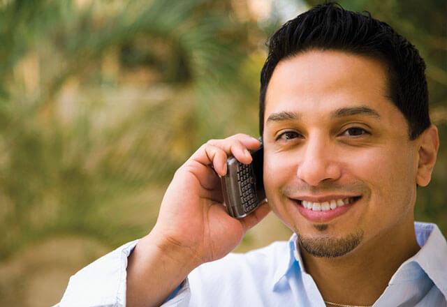 man talking on phone while smiling