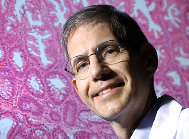 Gastroenterologist Francis Giardiello is shown with an image of colon cells
