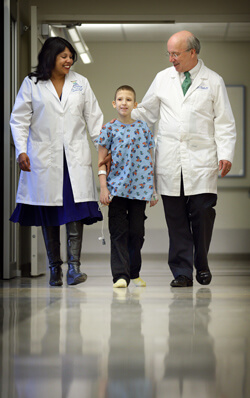 Sapna Kudchadkar and Frank Pidcock take a walk in the PICU with an 11-year-old patient a week after heart surgery. He began taking steps by day two.