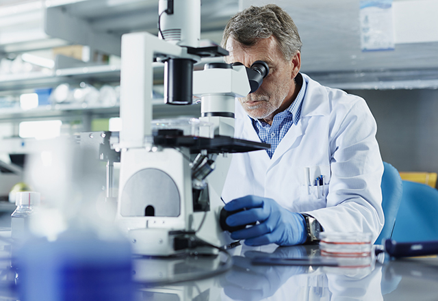 male researcher looking through microscope