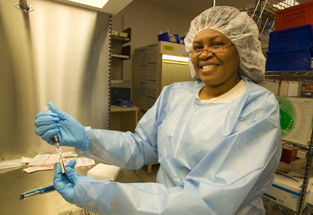 African-American female medical worker in scrubs holding a blood vial and syringe.